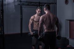 Un culturista del hombre joven, mirando se, llevando a cabo pesas de gimnasia Imagen de archivo