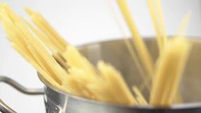 Un cuoco ha posato gli spaghetti in una pentola d'acciaio su un fondo bianco video d archivio