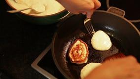 Un cuoco lancia sopra le frittelle nella padella stock footage