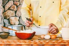 Un cuoco maschio in un indumento giallo sbatte la sbattitura la pastella, fotografie stock