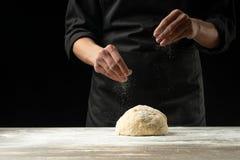 Un cuoco professionista in una cucina professionale prepara la pasta della farina per produrre la pasta bio--italiana concetto de fotografia stock libera da diritti