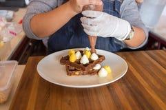 Un cuoco unico che aggiunge guarnizione crema sulle cialde su una tavola di legno Immagine Stock