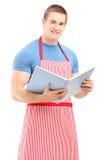 Un cuoco unico maschio che tiene un libro di cucina e che esamina macchina fotografica Fotografia Stock