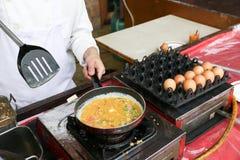 Un cuoco unico sta cucinando un'omelette Fotografia Stock Libera da Diritti