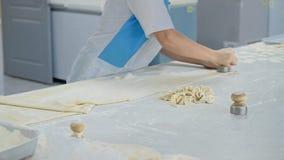 Un cuoco unico sta tagliando la pasta in cerchi per i ravioli stock footage