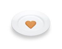 Un cuore del pan di zenzero che si trova su un piatto bianco Immagini Stock Libere da Diritti