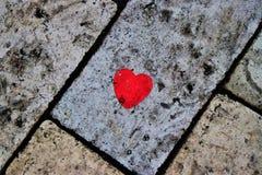 Un cuore di carta, incorniciato in un pavimento sporco del mattone Concetto di amore fotografia stock libera da diritti
