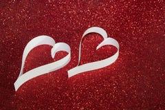 Un cuore di due bianchi da carta su fondo brillante rosso Fotografie Stock Libere da Diritti