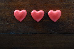 Un cuore di tre rossi su fondo di legno Immagini Stock