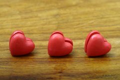 Un cuore di tre rossi su fondo di legno Immagine Stock Libera da Diritti
