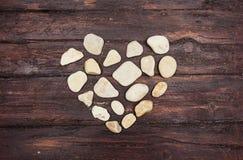 Un cuore ha modellato le pietre del ciottolo su un vecchio legno Fotografia Stock