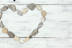Un cuore ha modellato le pietre del ciottolo su un vecchio legno Fotografie Stock Libere da Diritti
