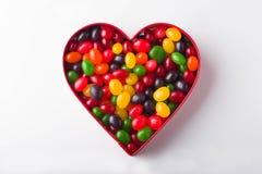 Un cuore in pieno dei Jellybeans colorati Multi su un fondo bianco fotografia stock