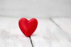 Un cuore rosso sull'bordi di legno bianchi Fotografia Stock