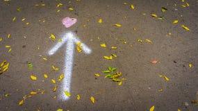 Un cuore tirato nella via con una freccia ed alle foglie di autunno sparse fotografie stock libere da diritti