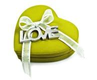 Un cuore verde con l'amore di parola ha spiegato in argento su bianco Immagini Stock