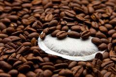 Un cuscinetto del caffè con molti chicchi di caffè Fotografia Stock