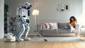 Un cyborg hoovering un cuarto con una señora en él metrajes