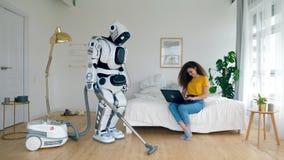 Un cyborg hoovering et une femme travaille sur un ordinateur portable banque de vidéos