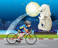 Un cycliste passant la rue avec Merlion Image libre de droits