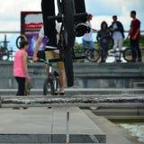 Un cycliste saute par-dessus un tuyau sur un vélo de BMX Beaucoup de personnes avec photographie stock
