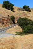 Un cycliste solitaire escaladant vers le haut une montagne Images stock