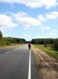 Un cycliste sur une route de campagne Photographie stock