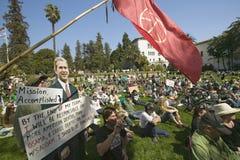 Un découpage de George W Bush indiquant la mission accomplie est vu avec une foule des protestataires et un drapeau rouge de paix Photos stock