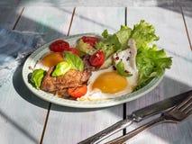 Un déjeuner chaleureux des oeufs au plat avec du foie et la tomate-cerise frits, laitue de feuille Service sur un plateau rustiqu photographie stock libre de droits