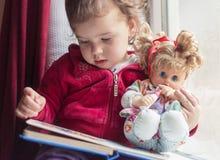 Un día lluvioso es el mejor para leer con su muñeca preferida foto de archivo