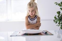 Un dîner de attente très furieux de petite fille photo stock
