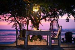Un dîner privé romantique de plage avec des bougies au coucher du soleil Images libres de droits