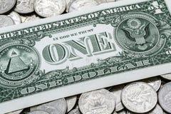 Un dólar Bill On de los E.E.U.U. una pila de cuartos Imagen de archivo