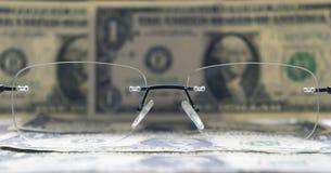 Un dólares de billetes de banco como un fondo y vidrios Foto de archivo libre de regalías