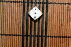 Un dado di plastica bianco sul fondo marrone del bordo di legno Sei cubi dei lati con i punti neri Numeri le presidenze di spiagg Fotografia Stock