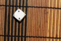 Un dado di plastica bianco sul fondo marrone del bordo di legno Sei cubi dei lati con i punti neri Numero 2 Fotografie Stock