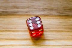 Un dado que juega exagonal rojo translúcido en un fondo de madera Foto de archivo libre de regalías