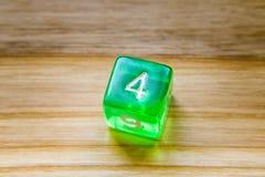 Un dado que juega exagonal verde translúcido en un backgroun de madera Fotos de archivo libres de regalías