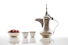Un dallah, un pot en métal pour faire le café arabe avec un bol de dattes sèches Photographie stock libre de droits