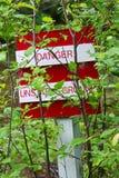 Un danger, signe au sol instable obscurci par des arbres Image stock