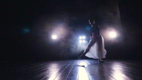 Un danseur classique féminin saute à travers une étape foncée banque de vidéos