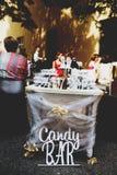 Un ` de la barra de caramelo del ` de las letras se coloca detrás de una tabla con los dulces Imagen de archivo libre de regalías