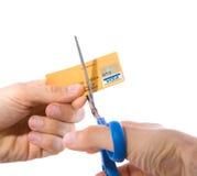 Un de la tarjeta de crédito que es cortada adentro dos con las tijeras Imagen de archivo libre de regalías