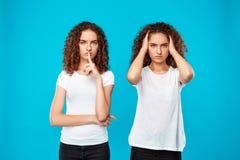 Un de représentation de jumelles de soeurs gardent le silence au-dessus du fond bleu photographie stock