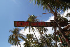 """Un  de worry†d'""""Don't d'inscription sur la hutte abandonnée en bois sur le fond de palmier et de ciel Photos stock"""