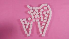 Un dente non sano con la carie è allineato con i cubi dello zucchero raffinato su un fondo rosa archivi video