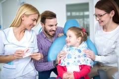 Un dentista de sexo femenino joven dice a una niña imagen de archivo libre de regalías