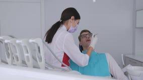 Un dentista de sexo femenino perfora un diente con un taladro a un paciente que se sienta en una silla dental almacen de metraje de vídeo