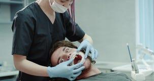 In un dentista dentario moderno della clinica che ripara la guardia di bocca al paziente lui sguardo divertente diritto alla macc archivi video