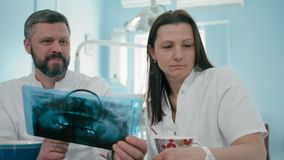 Un dentista di due medici sta esaminando la fotografia dei raggi x facendo uso della lente di ingrandimento e del computer portat stock footage